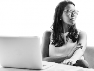 Black and white photo of a woman sitting in front of a laptop and looking off into the distance