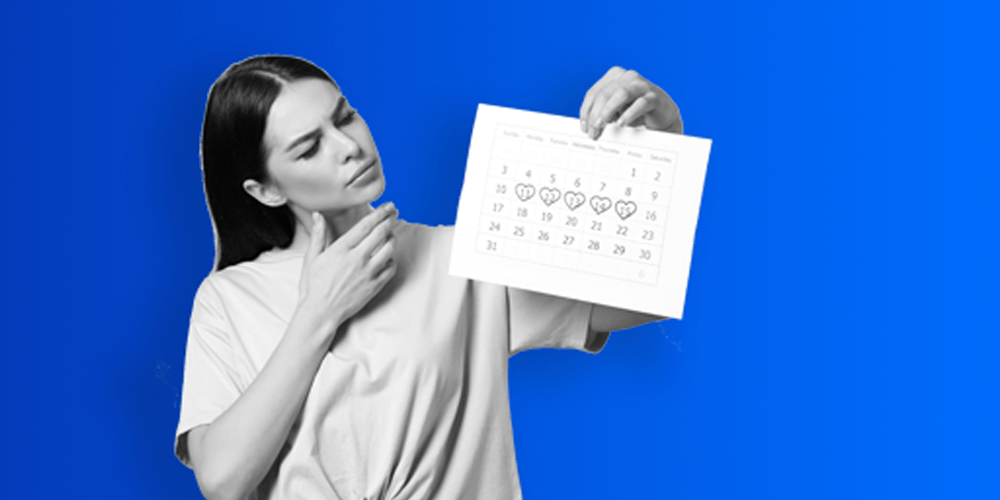 A woman holding up a monthly calendar with certain dates circled and looking at them.